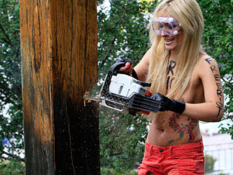 Hot half naked Russian chick chainsaws someone else's crucifix in Russia